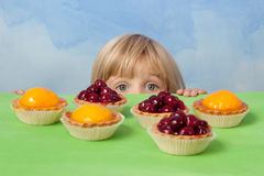 Little pretty girl with cherry and peach jelly tarts Stock Images