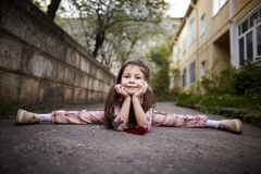Little pretty girl doing splits outdoors Stock Photo