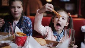 A little pretty girl drinks juice and eats French fries in fast food. fast food cafe stock footage
