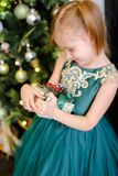 Little pretty girl with gift wearing dress and standing near Christmas tree. Concept of presents, childhood and winter holidays Royalty Free Stock Image