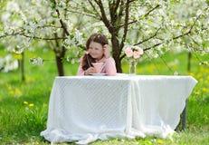 Little pretty girl in the green garden Stock Photo