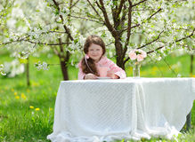 Little pretty girl in the green garden Royalty Free Stock Photo