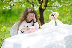 Little pretty girl in the green garden Stock Image