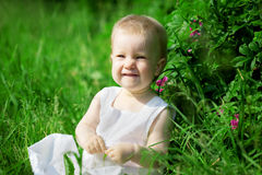 Little pretty girl on a green lawn Royalty Free Stock Photos