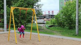 Little pretty girl in gumboots on swing at playground stock footage