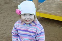 Little pretty girl in hat smiles on children playground Stock Photos