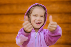 Little pretty girl lifts up thumb Stock Images
