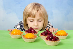 Little pretty girl looking at cherry and peach jelly tarts Royalty Free Stock Photography