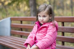 Little pretty girl in a pink coat sitting on a wood bench at the park in autumn royalty free stock photo