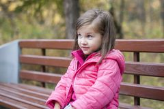Little pretty girl in a pink coat sitting on a wood bench at the park in autumn. Emotional portrait. Childhood concept. Caucasian. Child with brunette long Royalty Free Stock Image