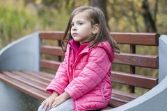 Little pretty girl in a pink coat sitting on a wood bench at the park in autumn. Emotional portrait stock photos