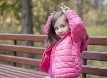 Little pretty girl in a pink coat sitting on a wood bench at the park in autumn. Emotional portrait. Childhood concept. Caucasian. Child with brunette long Stock Photo