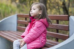 Little pretty girl in a pink coat sitting on a wood bench at the park in autumn. Emotional portrait. Childhood concept. Caucasian. Child with brunette long Stock Photography