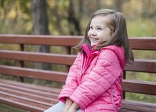 Little pretty girl in a pink coat sitting on a wood bench at the park in autumn. Emotional portrait. Childhood concept. Caucasian. Child with brunette long Royalty Free Stock Photography