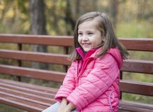 Little pretty girl in a pink coat sitting on a wood bench at the park in autumn. Emotional portrait. Childhood concept. Caucasian. Child with brunette long Royalty Free Stock Photos