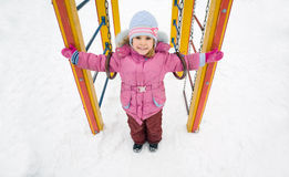 Little pretty girl on playground in winter Stock Photography