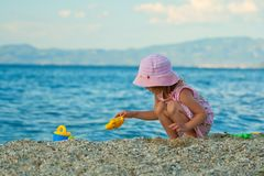 Little pretty girl playing on the beach. Royalty Free Stock Images