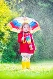 Little pretty girl playing in the rain. Funny cute curly toddler girl wearing red waterproof coat and yellow rubber boots holding colorful umbrella playing in Stock Photo