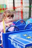 Little pretty girl rides on bright car in amusement park Stock Photography