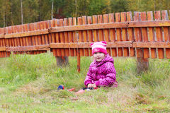 Little pretty girl sits in grass near orange wooden fence Stock Images