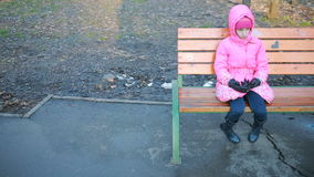 Little pretty girl sitting on a bench and sad at the park in autumn stock video