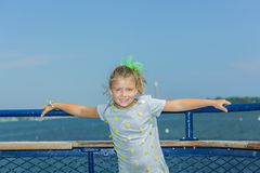 Little pretty girl standing on the boat deck against blue lake and sky background Stock Photos