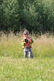 Little pretty girl stands on green grass and holds camera Royalty Free Stock Photography