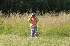 Little pretty girl stands on green grass and shoots Royalty Free Stock Image