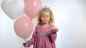 A little pretty girl three years old with balloons eats donut in her birthday, isolated over white background stock footage