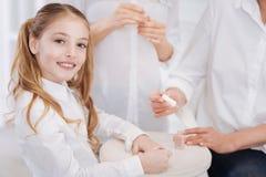 Little pretty girl using nail polish Stock Photography