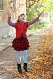 Little pretty girl in vest throws up leaves Stock Photography