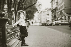 Little pretty girl walking on the city street Stock Photo