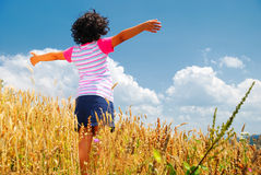 A little pretty girl on wheat field. With hands up Royalty Free Stock Image