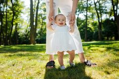 Little pretty girl in white dress holds mom by the hands and tries to make her first steps. royalty free stock photo