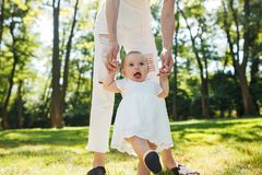 Little pretty girl in white dress holds mom by the hands and tries to make her first steps. stock photo