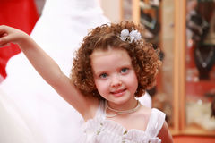 Little, pretty girl in a white girls' gown. Stock Photo
