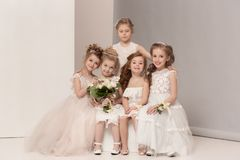 Little pretty girls with flowers dressed in wedding dresses Stock Photo
