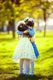 Little pretty girls having fun outdoor. Two cute girls are standing on green grass and hugging. Best friends stock photos