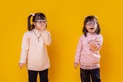 Little pretty girls with mental disorder wearing pink sweaters stock photo
