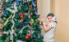 Little  pretty happy girl decorating and preparing a Christmas tree in her room Royalty Free Stock Photo