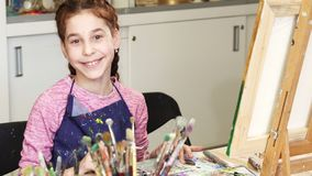 Little happy beautiful girl smiling to the camera at the art studio. Little pretty happy girl enjoying working on a painting at the art class smiling to the royalty free stock photo