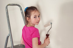 Little pretty house-painter. Girl with a paddle roller staying on the duckboard Royalty Free Stock Image