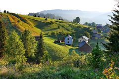 Little pretty houses with a backdrop of gently sloping green mountains. For your design stock images
