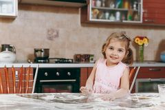 Little pretty kid girl in pink dress playing, smearing hands and face with flour in light kitchen at table. Child royalty free stock images