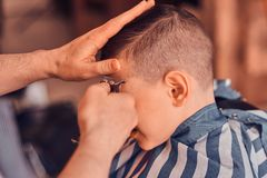 Little pretty school boy had his first trendy haircut at modern barbershop.  royalty free stock photo