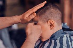 Little pretty school boy had his first trendy haircut at modern barbershop.  stock photos
