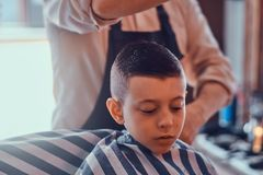 Little pretty school boy had his first trendy haircut at modern barbershop.  stock images