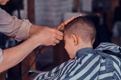 Little pretty school boy had his first trendy haircut at modern barbershop.  royalty free stock image