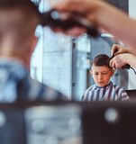 Little pretty school boy had his first trendy haircut at modern barbershop.  royalty free stock photos