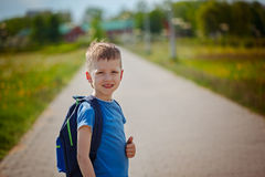 Little pretty schoolboy sitanding on the street with his backpac Royalty Free Stock Image